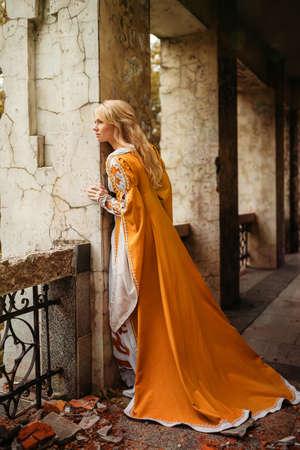 Bella donna bionda in abito a piedi medioevale vicino a vecchia costruzione