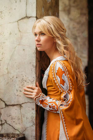 traditional dress: Beautiful blond woman in medieval dress walking near old building