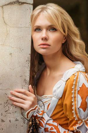 Mooie blonde vrouw in middeleeuwse jurk lopen in de buurt van oude gebouw