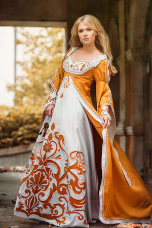 Beautiful blond woman in medieval dress walking near old building