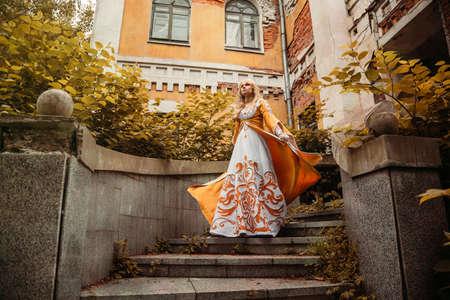 vestido medieval: hermosa mujer rubia en traje medieval a pie cerca del edificio viejo