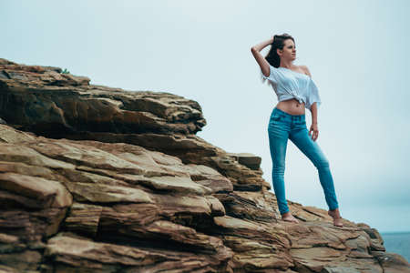 wet jeans: Young charming woman in wet jeans on the beach