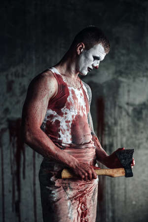vindictive: Crazy clown holding an ax in his hands