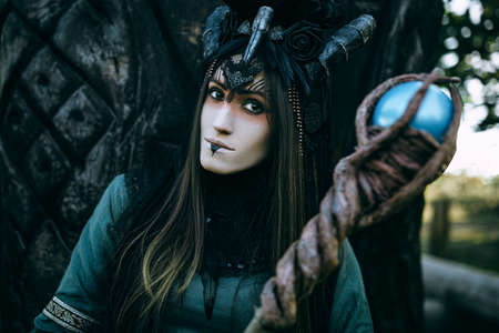 necromancer: Woman-shaman with horns in green dress walk in forest