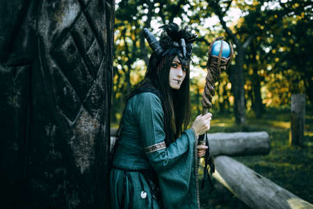 exorcist: Woman-shaman with horns in green dress walk in forest