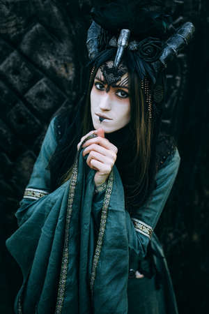 pagan: Woman-shaman with horns in green dress walk in forest