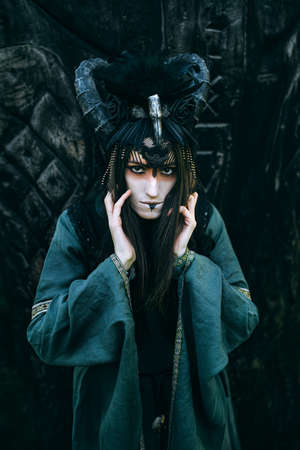 mystical: Woman-shaman with horns in green dress walk in forest