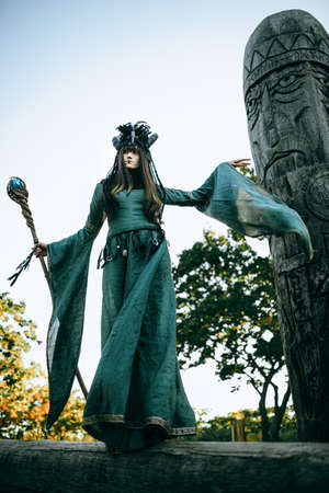 legends: Woman-shaman with horns in green dress walk in forest