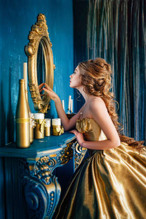 Beautiful woman in a golden ball gown in the great blue interior 스톡 콘텐츠