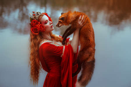 A young woman in medieval red dress with a fox Foto de archivo