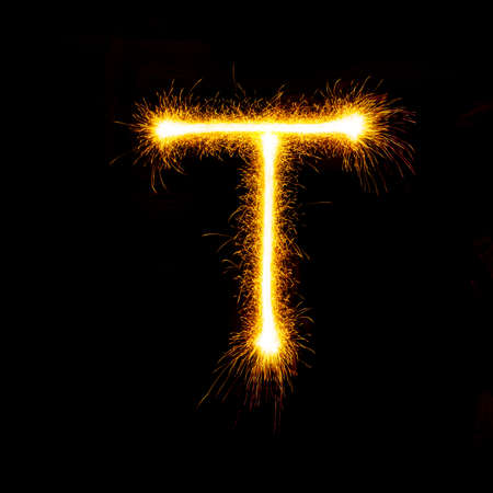 Alphabet sparklers on black background single letter