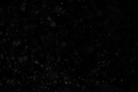 Abstract real dust floating over black background