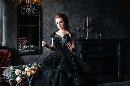 Attractive woman in black dress in medieval interior Stok Fotoğraf