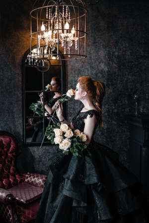 Attractive woman in black dress in medieval interior Imagens