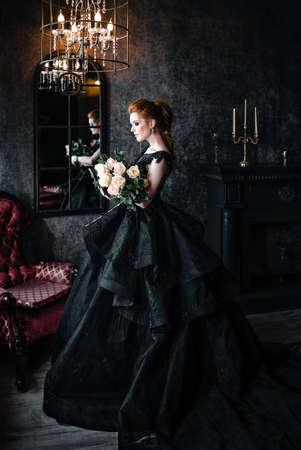 Attraktive Frau im schwarzen Kleid im mittelalterlichen Interieur Standard-Bild