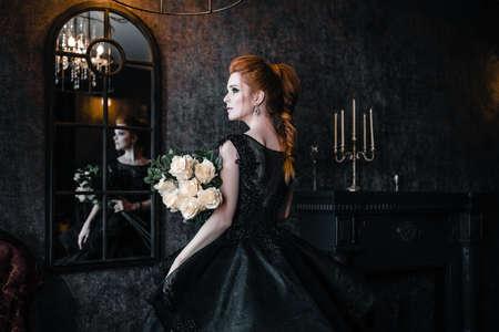 Mujer atractiva en vestido negro en interior medieval Foto de archivo