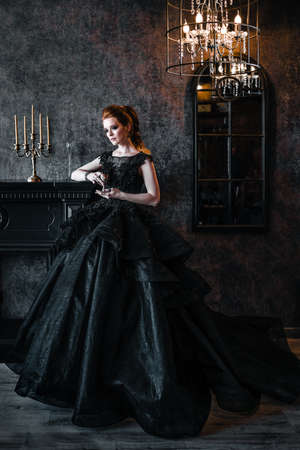 Attractive woman in black dress in medieval interior Stok Fotoğraf