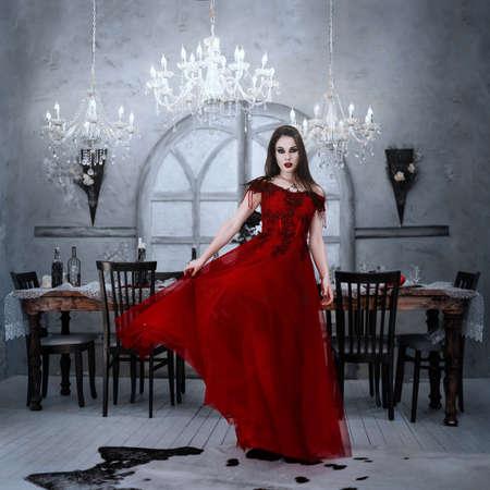 Bloodthirsty female vampire in red dress. Medieval interior