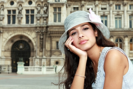 Beautiful young woman in a fashion pose in a Parisian plaza