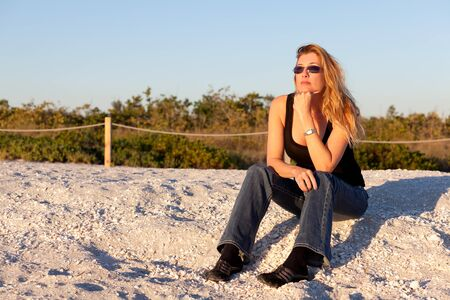Pretty Middle Age Blond Woman at the Beach in the late afternoon.