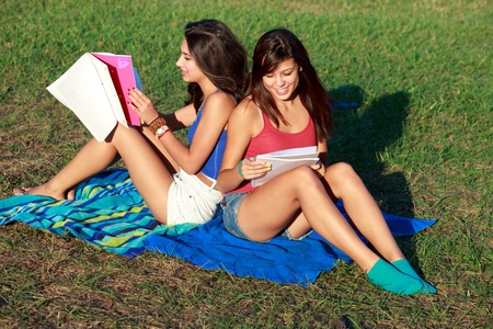 Pretty multiracial college roommates studying outdoors on a university campus photo