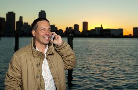 Handsome Hispanic Man on a Mobile Phone with downtown skyline photo