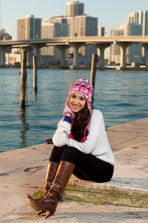 Pretty young woman in winter clothing along the bay at sunset
