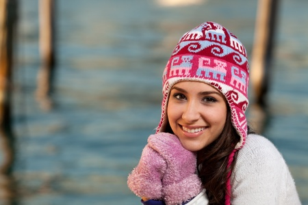 winter woman: Pretty young woman in winter clothing along the bay at sunset