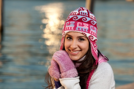 winter: Pretty young woman in winter clothing along the bay at sunset