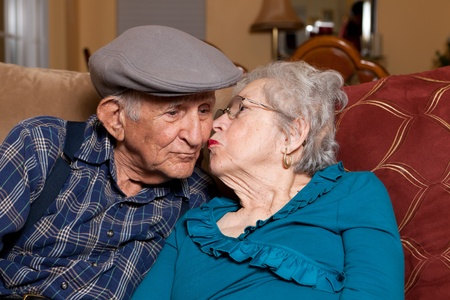 smooch: Elderly husband and wife in their 80s in an affectionate pose in a home lifestyle scene.