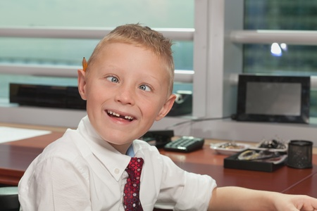 Cute Young Boy in Business Office with Funny Expression photo