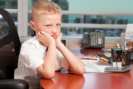 Young Boy in Business Office with Mad Expression photo