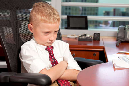 Young Boy in Business Office with Sad Expression photo