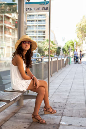 french ethnicity: Pretty Girl Waiting for a Bus in the French Riviera