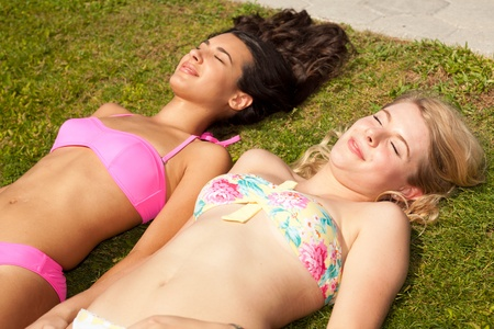 tanning: Pretty young blond and brunette sunbathing Stock Photo