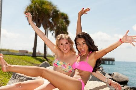 teen girl bikini: Pretty young blonde and brunette women wearing bikinis enjoying the beach Stock Photo