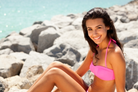 Pretty young brunette woman wearing a bikini enjoying the beach
