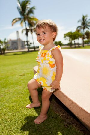 Cute baby girl outdoors in a park setting photo