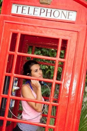 cabina telefonica: Bastante joven mujer en una cabina de teléfono rojo de época Foto de archivo