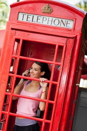 cabina telefono: Bastante joven mujer en una cabina de tel�fono rojo de �poca Foto de archivo