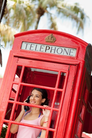 Pretty young woman in a vintage red telephone booth photo