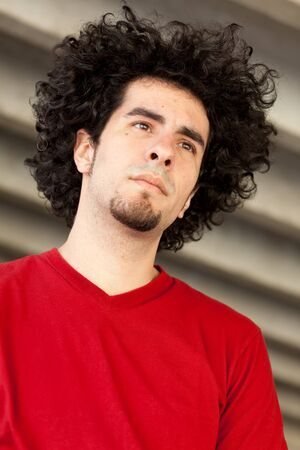 Handsome young man with long curly hair and goatee outdoors