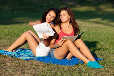 Pretty female college students studying on a campus field photo