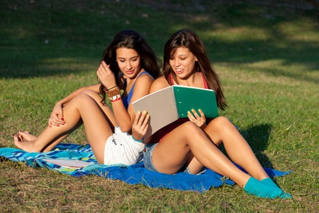 field study: Pretty female college students studying on a campus field