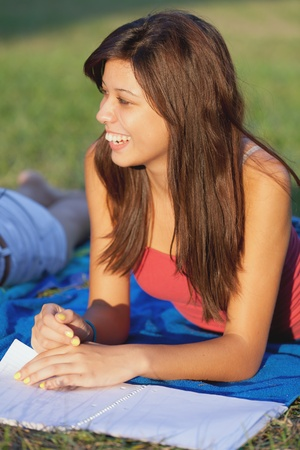 Pretty female college student studying on a campus field photo