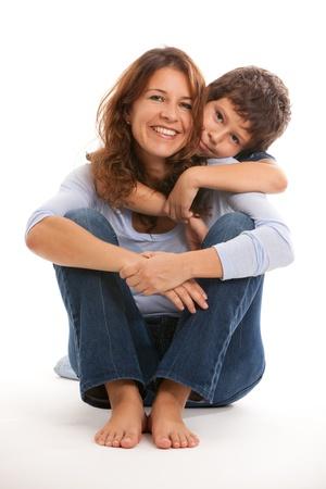 piedi nudi ragazzo: Madre e figlio in un affettuoso posa su uno sfondo bianco