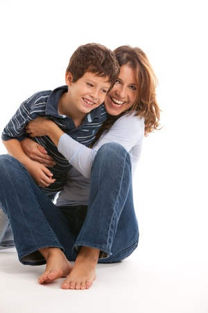 tickling: Mother tickling son and having fun on a white background Stock Photo