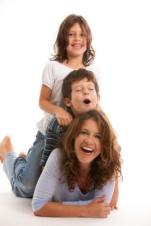 madre e hijo: Madre, hijo e hija se divierten en un fondo blanco Foto de archivo