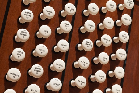 Close up view of the stop knobs of a church pipe organ photo