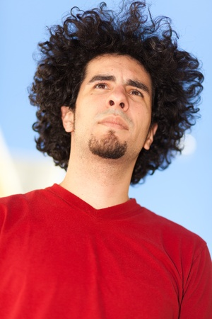 Handsome young man with long curly hair and goatee outdoors photo